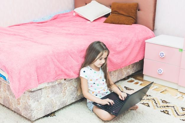 Bambina sveglia che si siede nella camera da letto facendo uso del computer portatile