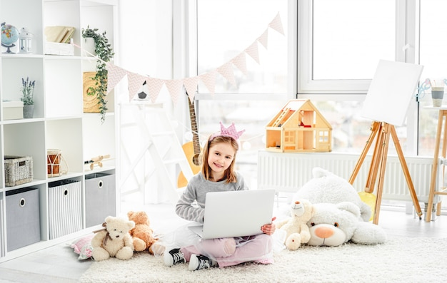 Bambina sveglia che si siede sul pavimento con il computer portatile in stanza dei giochi