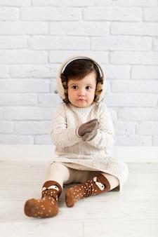 Bambina sveglia che si siede sul pavimento