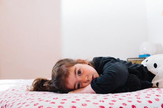 Bambina sveglia che si trova sul letto