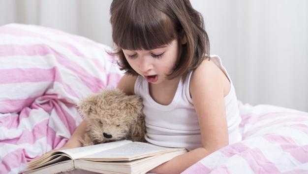 Bambina sveglia che sorride mentre trovandosi in un letto bianco accogliente