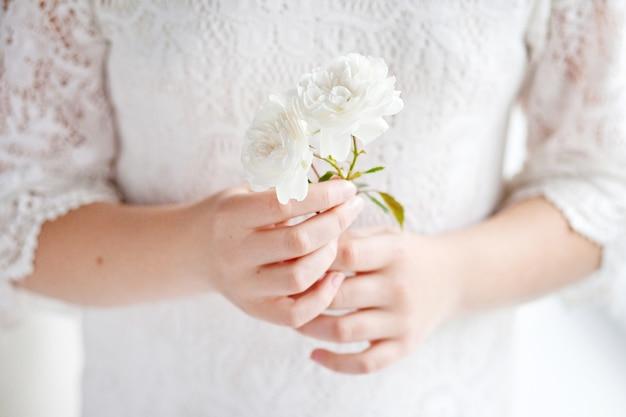 Bambina sveglia che tiene un fiore di rosa. i fiori nelle mani femminili si chiudono