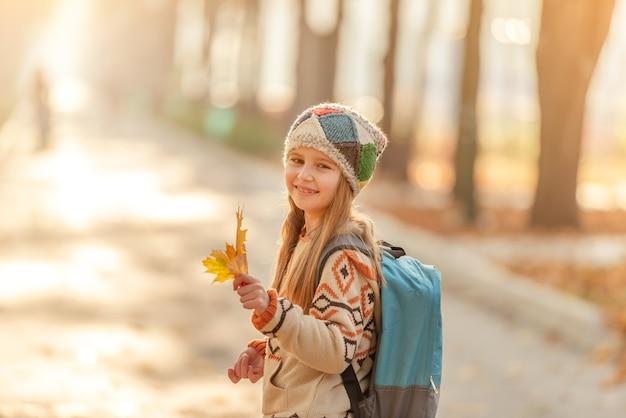 Bambina sveglia che va a scuola attraverso il parco d'autunno