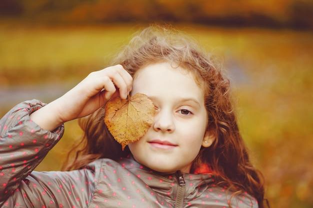 Bambina sveglia con foglie d'autunno