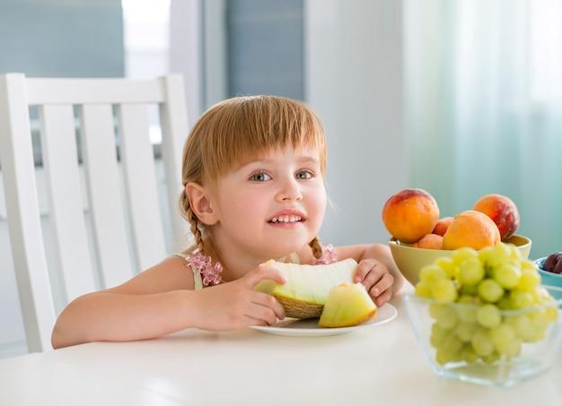 Bambina sveglia con i frutti sul tavolo