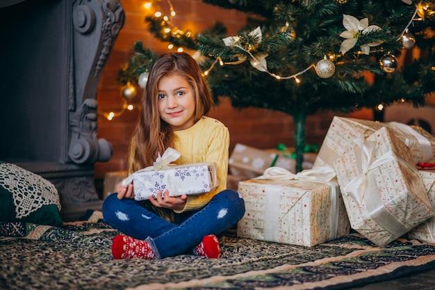 Bambina sveglia con i regali dall'albero di natale