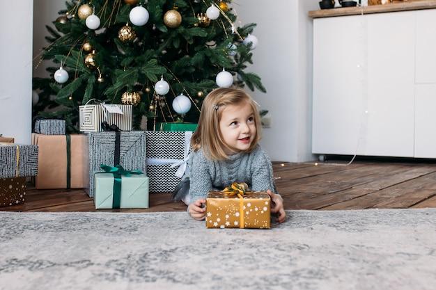 Bambina sveglia con i regali di natale