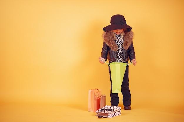 Bambina sveglia con i sacchetti della spesa su un fondo giallo