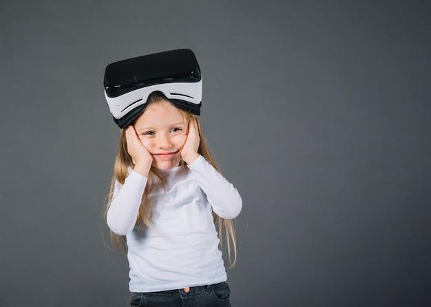 Bambina sveglia con i vetri di realtà virtuale sulla testa che tiene le sue guancie