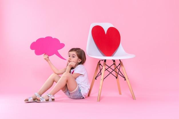Bambina sveglia con l'icona di discorso su colorato