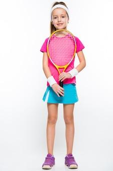 Bambina sveglia con la racchetta di tennis in sue mani su bianco