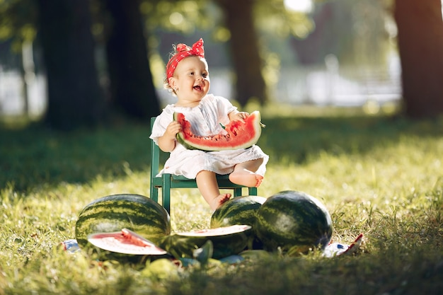 Bambina sveglia con le angurie in un parco