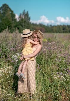 Bambina sveglia con sua madre che cammina nel giacimento di fiori