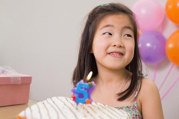 Bambina sveglia con torta alla sua festa di compleanno