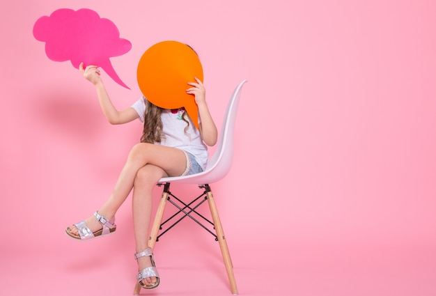 Bambina sveglia con un'icona di un discorso sul rosa