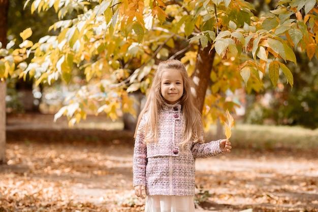 Bambina sveglia di 5 anni con foglie d'arancio autunnali in autunno nel parco