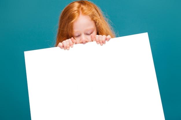 Bambina sveglia di bellezza in maglietta con il cartello pulito della tenuta dei capelli lunghi