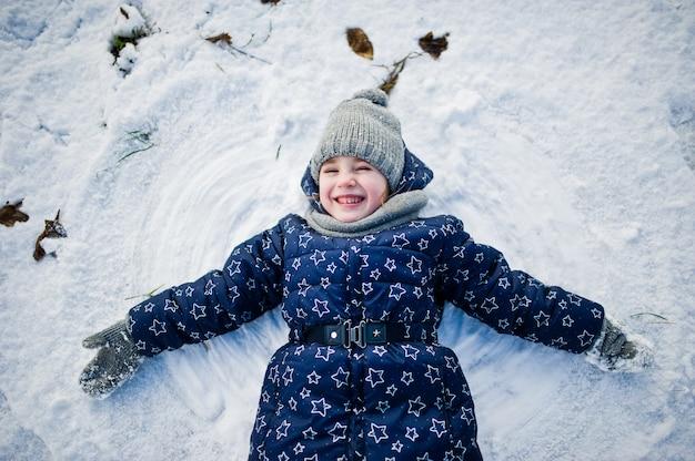 Bambina sveglia divertendosi all'aperto il giorno di inverno.