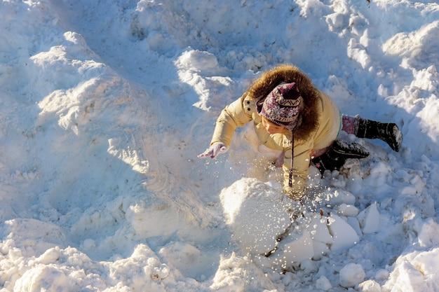 Bambina sveglia divertendosi in precipitazioni nevose. i bambini giocano all'aperto stagione invernale nella neve.