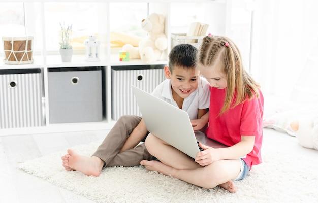 Bambina sveglia e ragazzo che per mezzo del computer