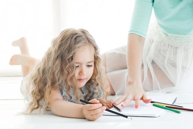 Bambina sveglia e sua madre che disegnano insieme un'immagine all'interno.