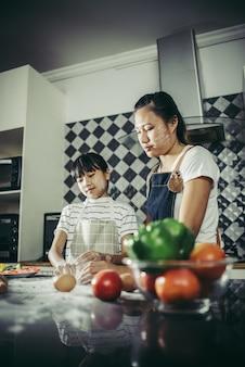 Bambina sveglia e sua madre in grembiuli che appiattiscono la pasta facendo uso di un matterello nella cucina