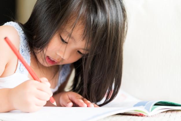 Bambina sveglia felice che sorride e che tiene matita e disegno rossi.