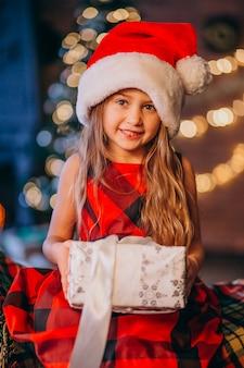 Bambina sveglia in cappello della santa che disimballa regalo di natale