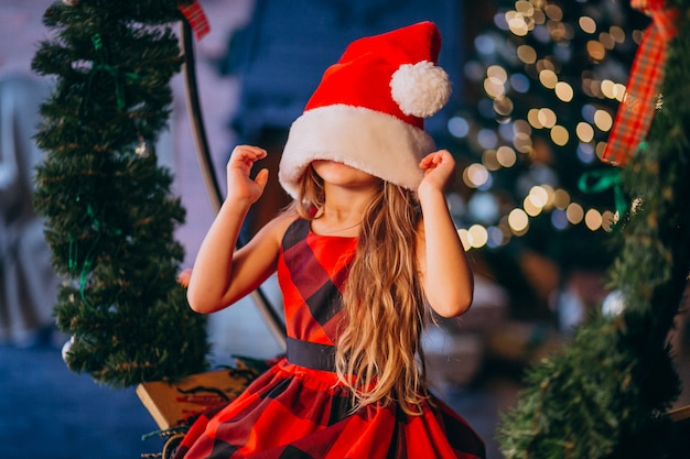 Bambina sveglia in cappello della santa e vestito rosso