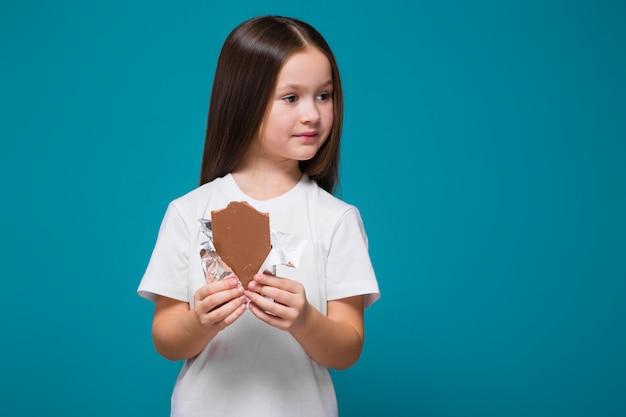 Bambina sveglia in maglietta con i capelli lunghi, con candy bar in mano