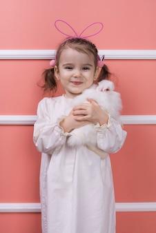 Bambina sveglia in orecchie di coniglio con coniglio