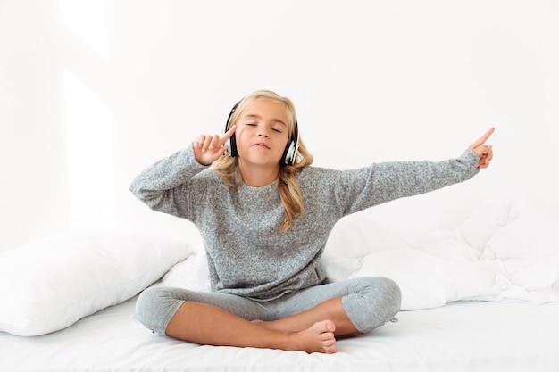 Bambina sveglia in pigiama grigio che ascolta la musica con gli occhi chiusi mentre sedendosi nel suo letto