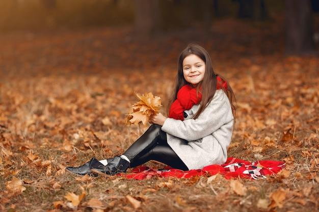 Bambina sveglia in un cappotto grigio che gioca in un parco di autunno