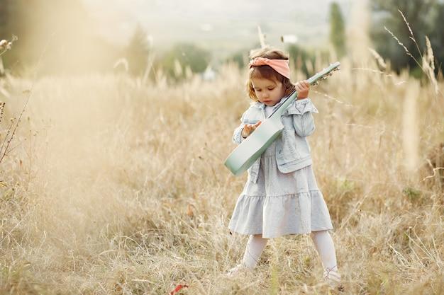 Bambina sveglia in un parco che gioca su una chitarra