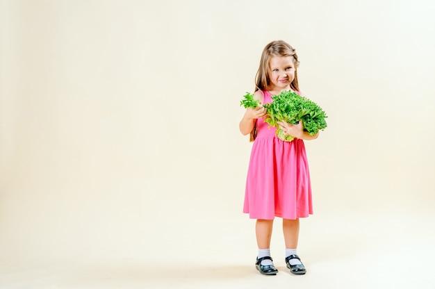 Bambina sveglia in un vestito rosa che tiene lattuga fresca.