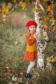 Bambina sveglia in vestiti a maglia nella sosta di autunno