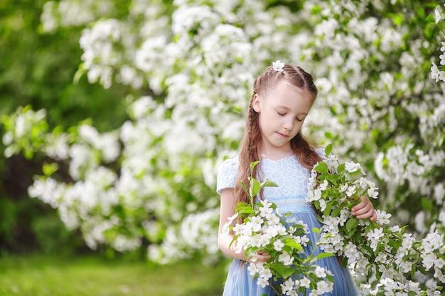Bambina sveglia nel giardino di fioritura di melo alla molla