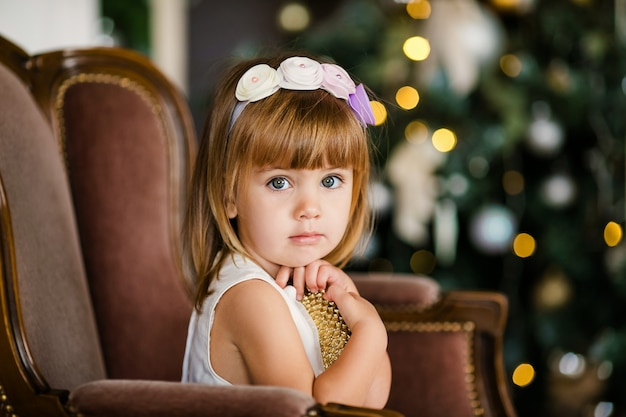 Bambina sveglia nel vestito bianco con bella corona vicino all'albero di natale