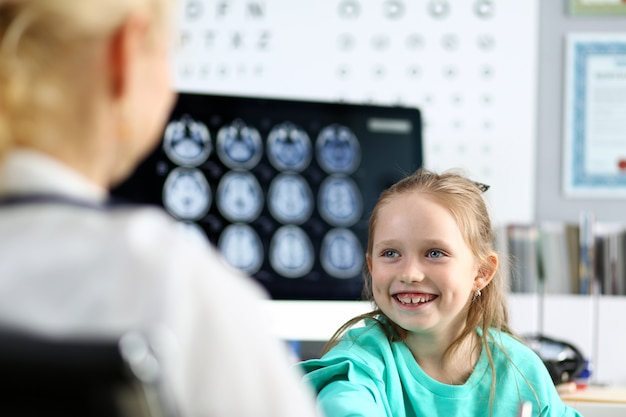 Bambina sveglia sorridente che parla con medico femminile nel suo ufficio
