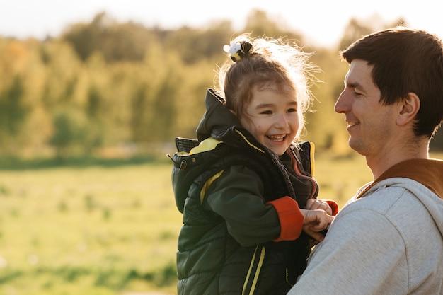 Bambina tra le braccia di papà che ride