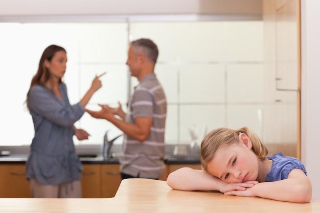 Bambina triste che ascolta i suoi genitori che hanno una discussione