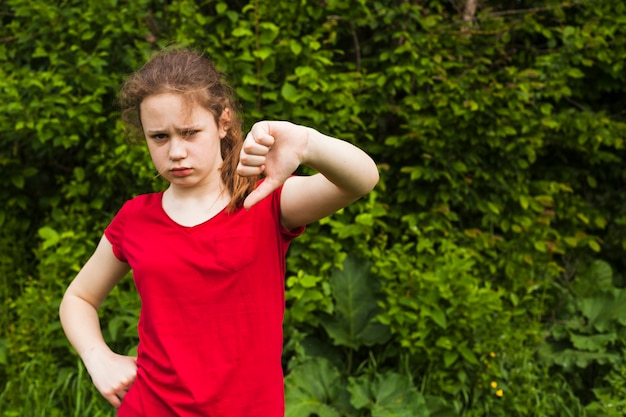 Bambina triste che mostra gesto di avversione nel parco