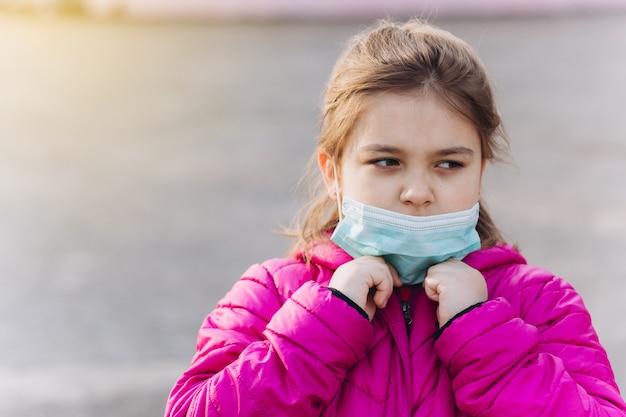 Bambina triste e depressa in protettivo medico sterile dalla mascherina del virus all'aperto. assistenza sanitaria, epidemia, pandemia, concetto di malattia