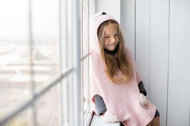 Bambina vestita inverno accanto a una finestra