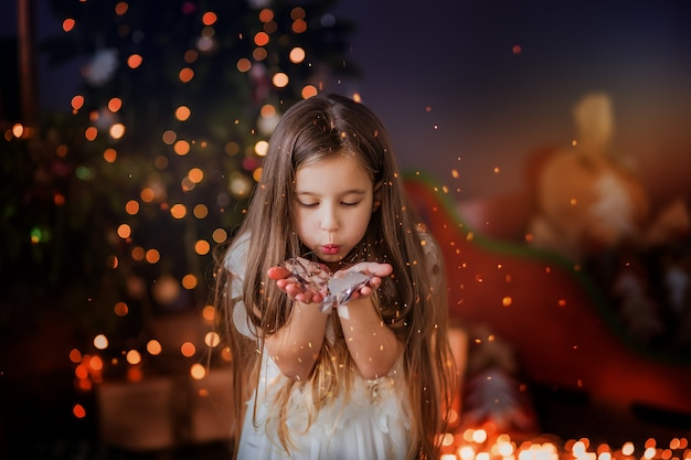 Bambina vicino all'albero di natale che sorride