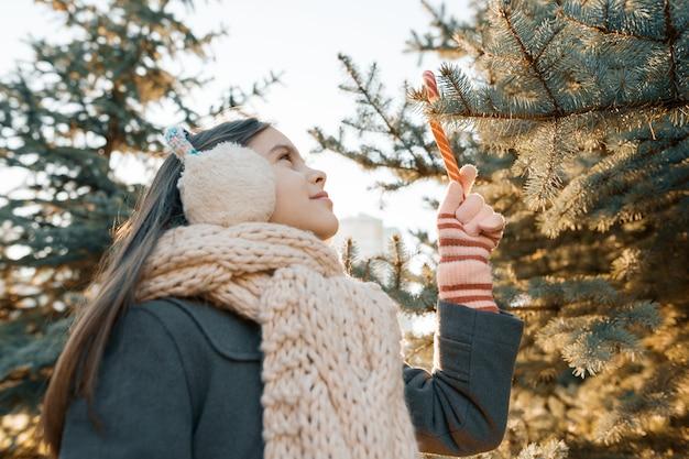 Bambina vicino all'albero di natale con i bastoncini di zucchero tradizionali