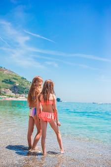 Bambine adorabili che giocano con la sabbia sulla spiaggia. vista posteriore di bambini che camminano lungo la spiaggia