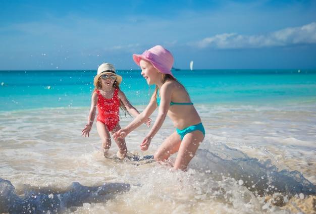 Bambine adorabili che giocano in acque basse alla spiaggia esotica