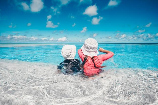 Bambine adorabili che giocano nella piscina all'aperto in vacanza