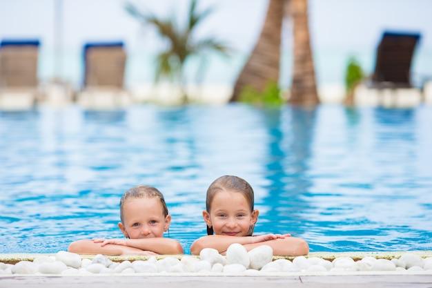 Bambine adorabili che giocano nella piscina all'aperto